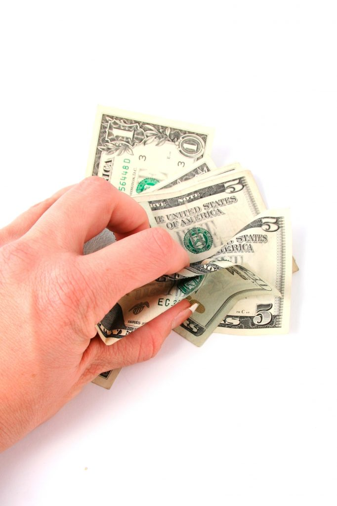 Woman's hand clutching five and one dollar bills
