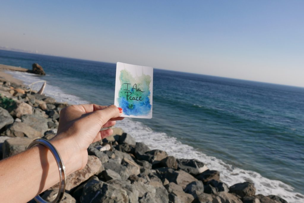 "Woman's hand with bracelet holding card with statement ""I Am Peace"" in front of rocky ocean shore"