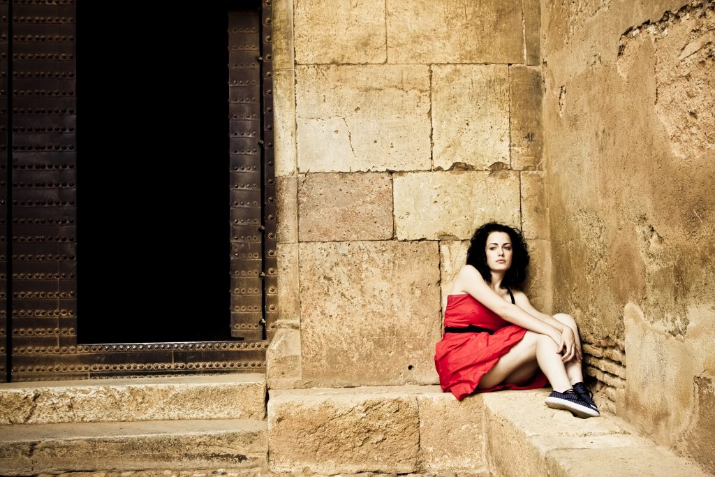 Sad young woman in red dress tucked into a corner of a stone building
