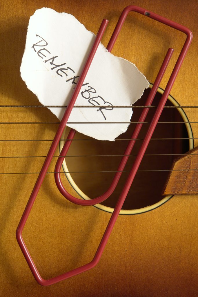 """Torn note with the words """"Remember"""" paperclipped to guitar strings"""