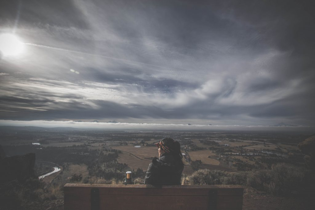 Woman sittin on bench surveying expansive landscape vista